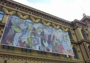 Monumentaaliteos Juhlat kaupungissa koristaa ateneumin julkisivua. Tove Jansson vetää röökiä kuvan etuosassa.