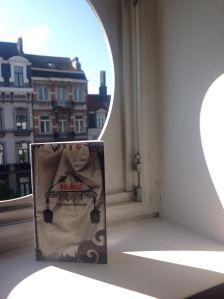 Matkalukemisto nähtynä hotellihuoneen ikkunan valossa